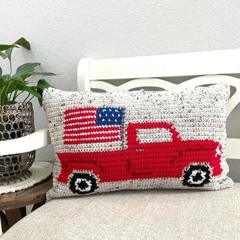 Crocheted pillow with red truck and American flag on it.