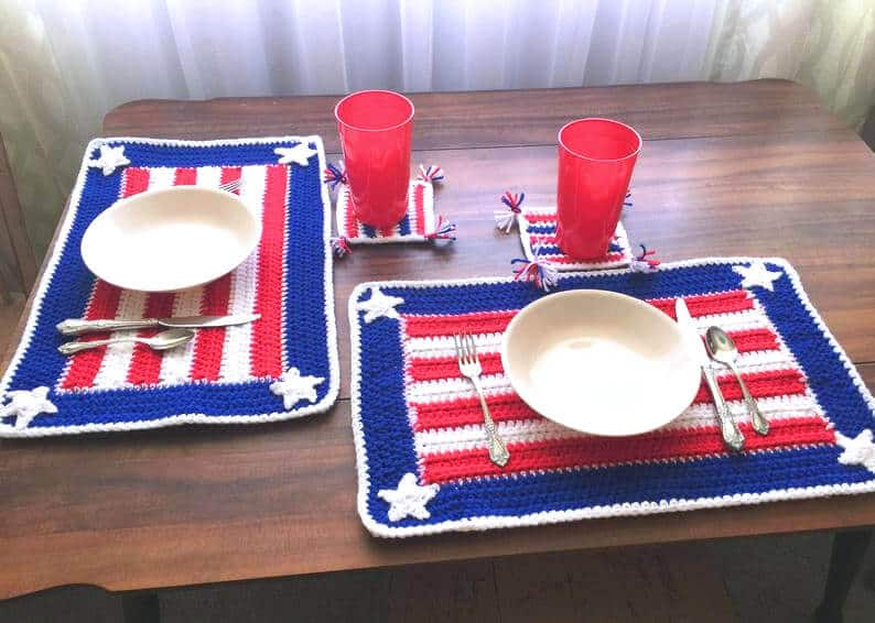 Crocheted placemats in red, white and blue colors, plates, cups and silverware.