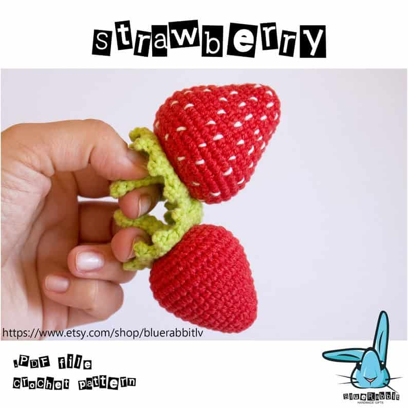 Two crocheted strawberries being held by a hand.