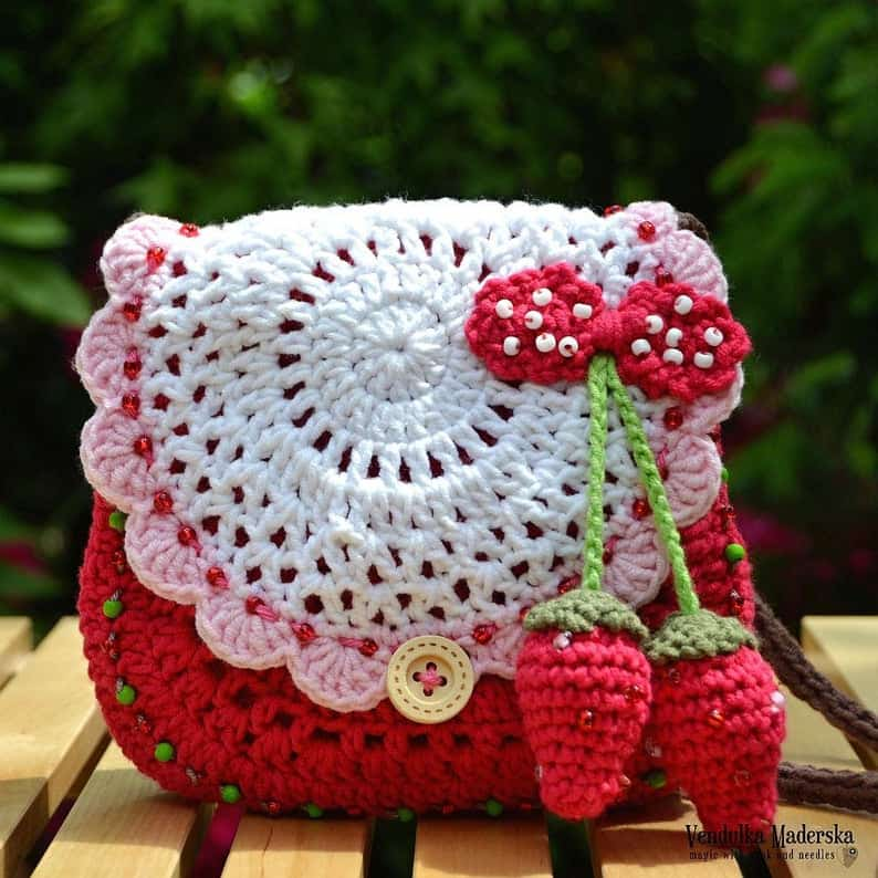 Crocheted handbad with two small crocheted strawberries attached to it.