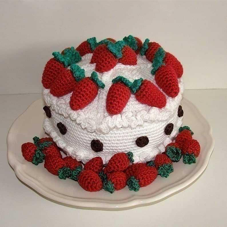 Crocheted cake with crocheted strawberries on top and around it.