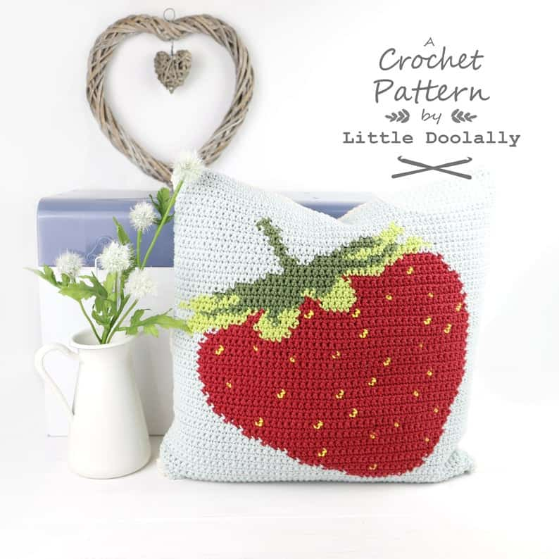 Crocheted pillow with strawberry image on it.