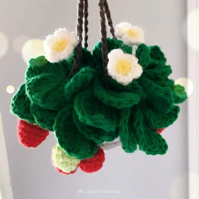 Crocheted strawberry plant in a hanging basket.