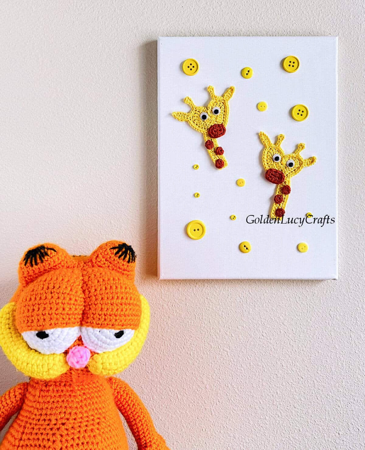 Two crocheted giraffe appliques on white canvas hanging on the wall, crocheted Garfield toy sitting next to it.