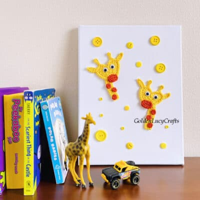 Two crocheted giraffe appliques on white canvas, baby books, small giraffe toy and small truck toy.