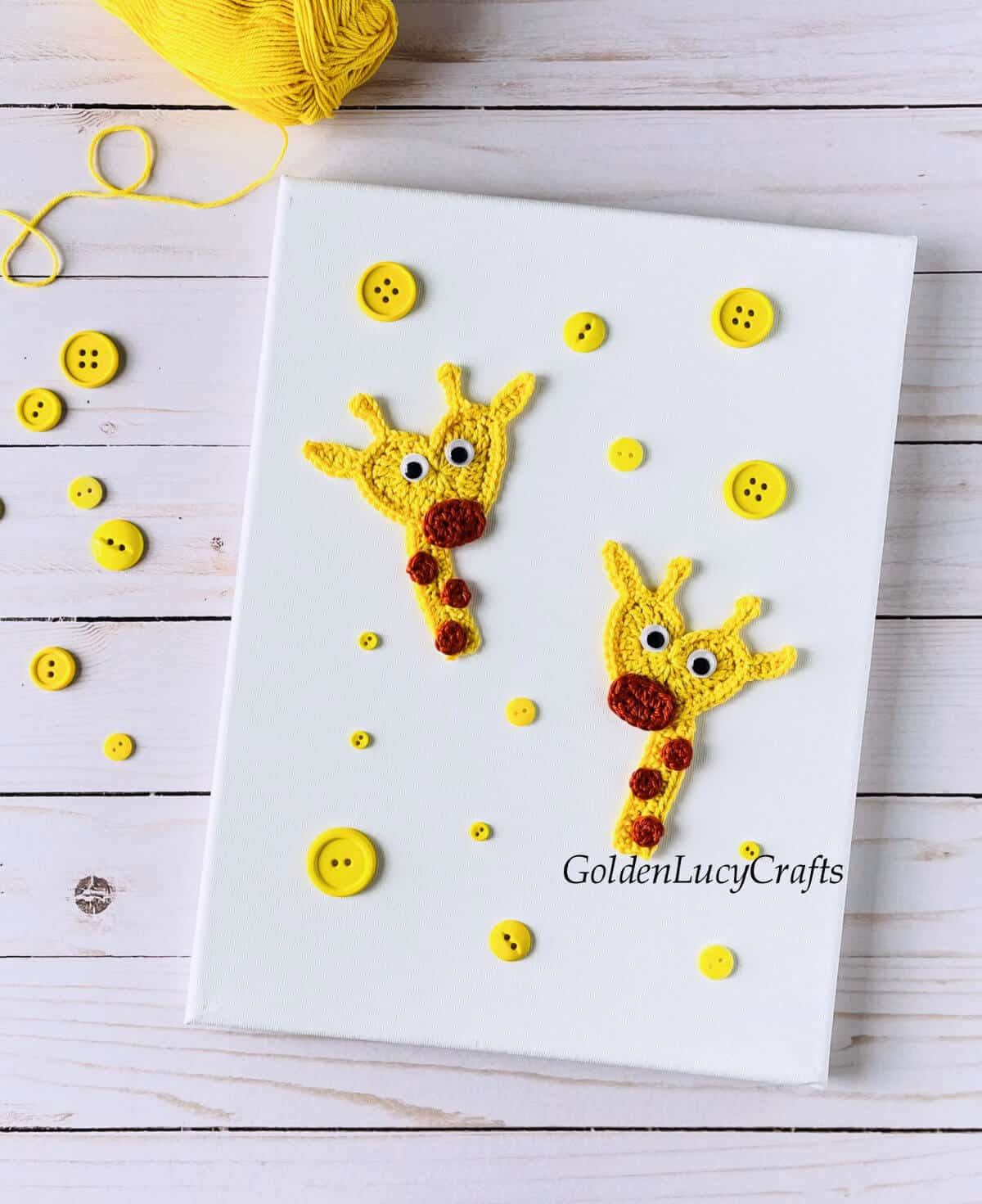 Two giraffe appliques on white canvas, yellow buttons and yellow skein of yarn.