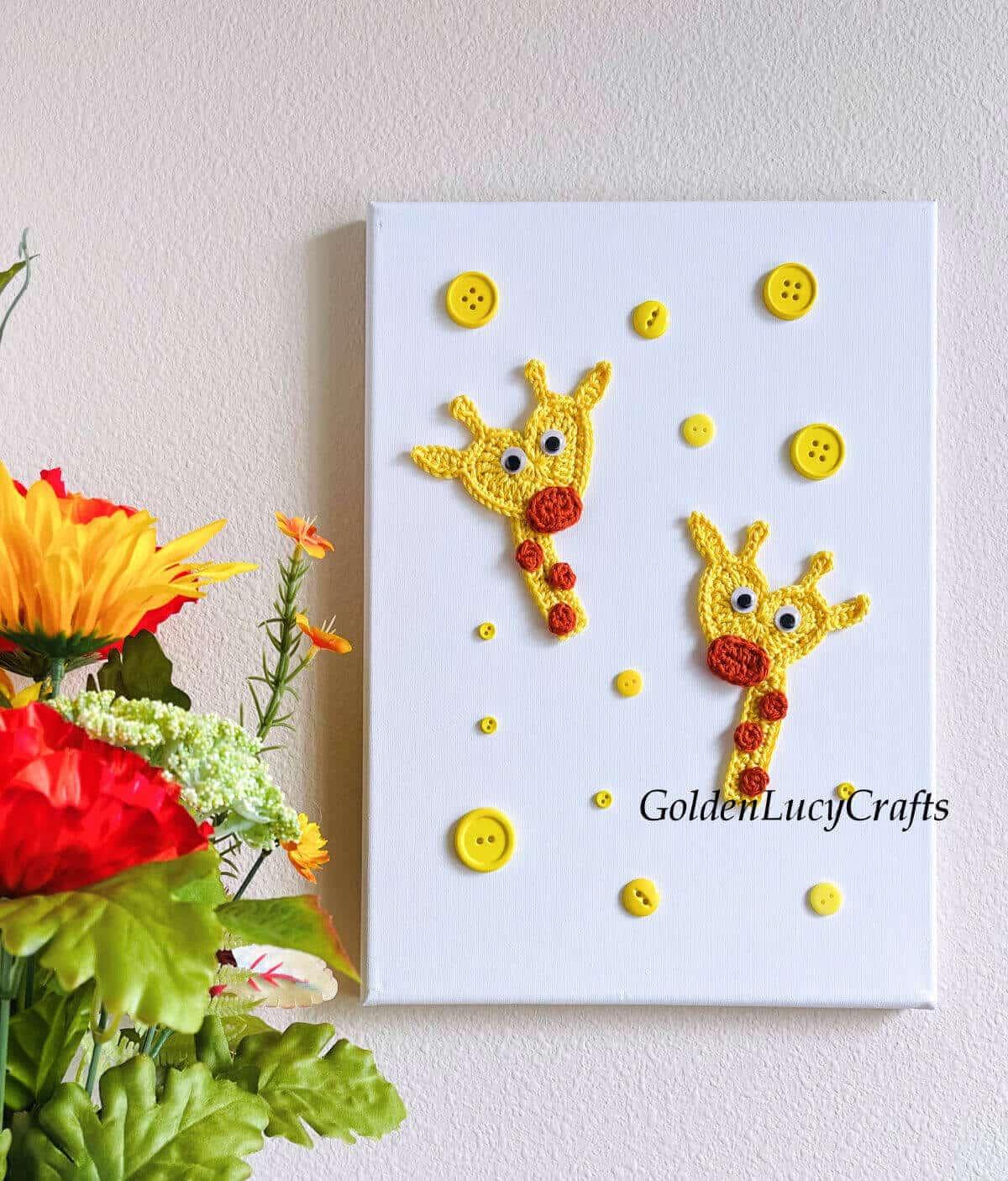 Crocheted giraffe wall decor, flowers next to it.