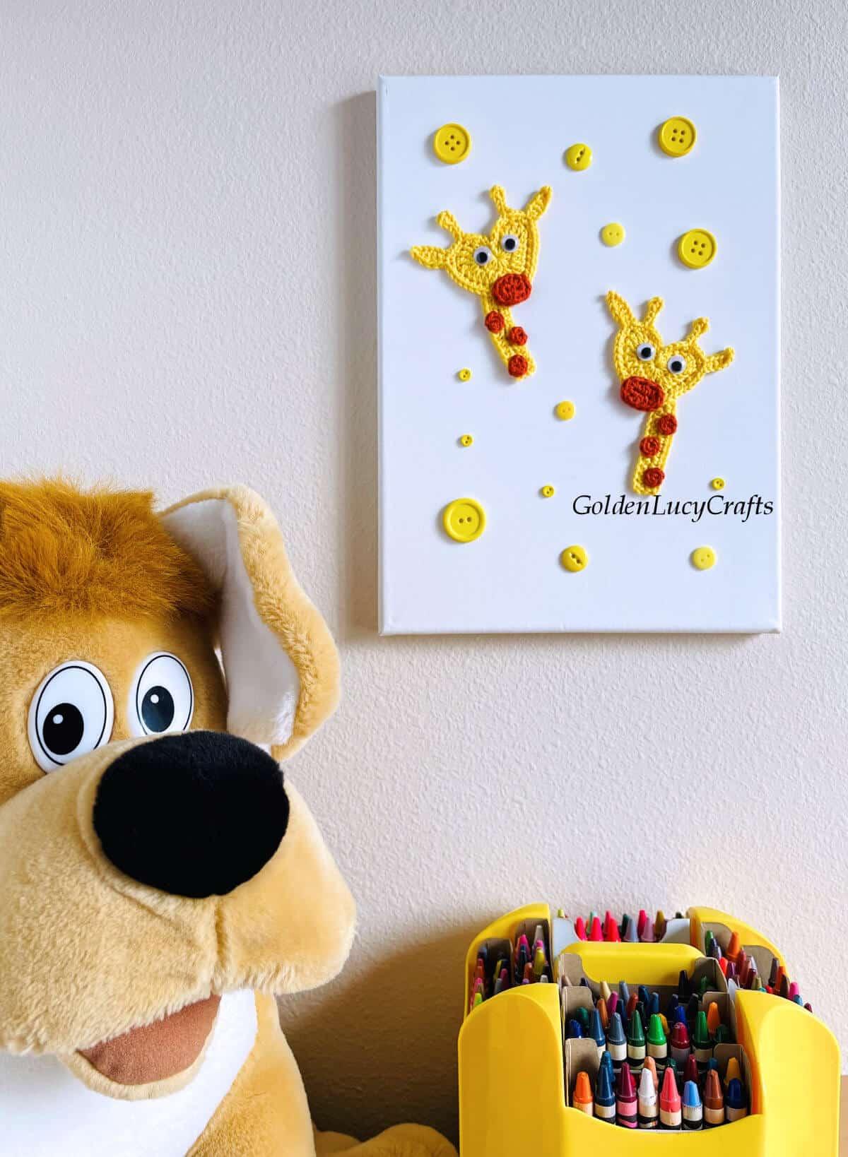 Giraffe crochet wall hanging, dog toy next to it.