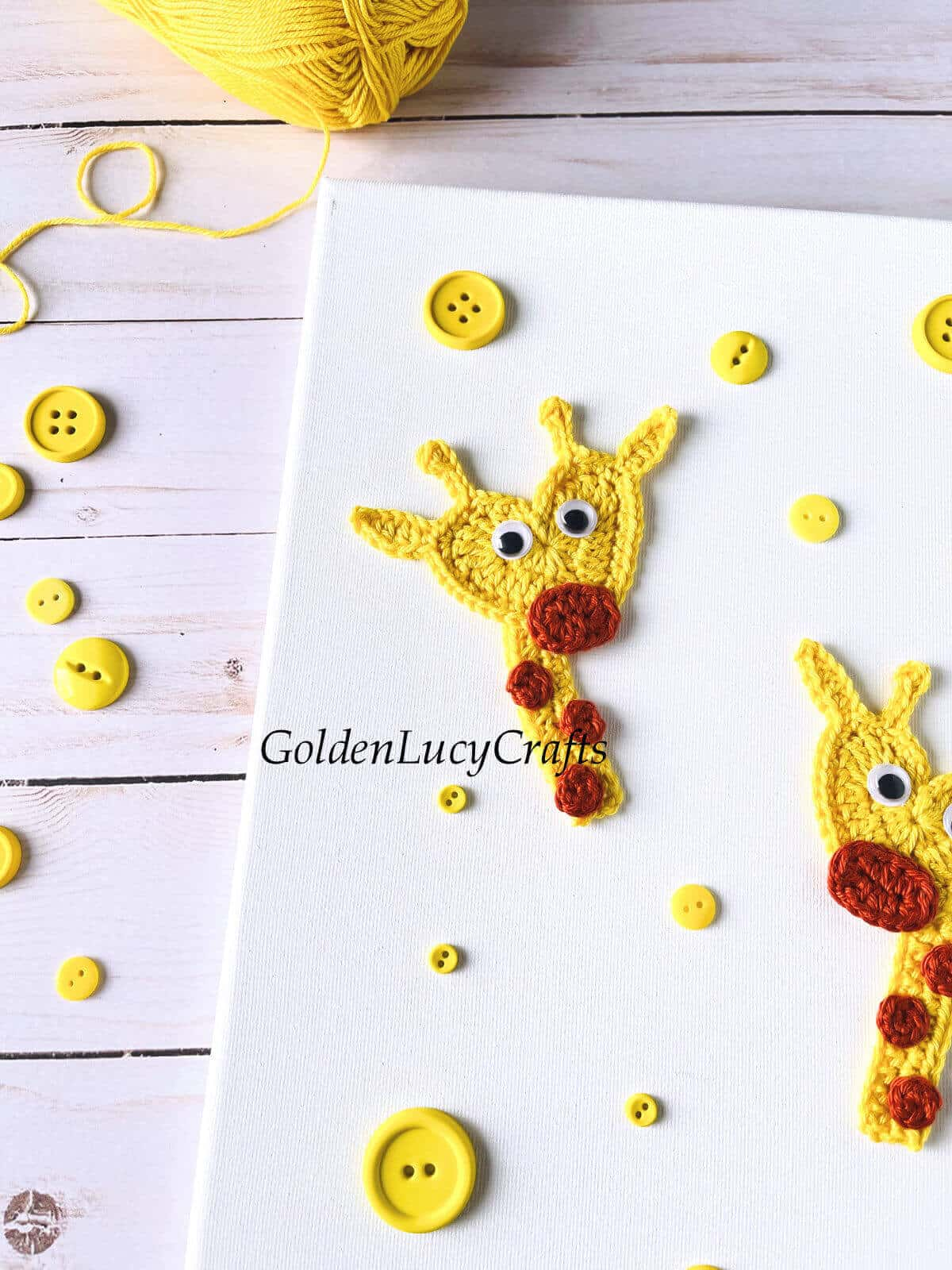 Two crochet giraffe appliques on canvas, yellow buttons, yellow yarn - close up picture.