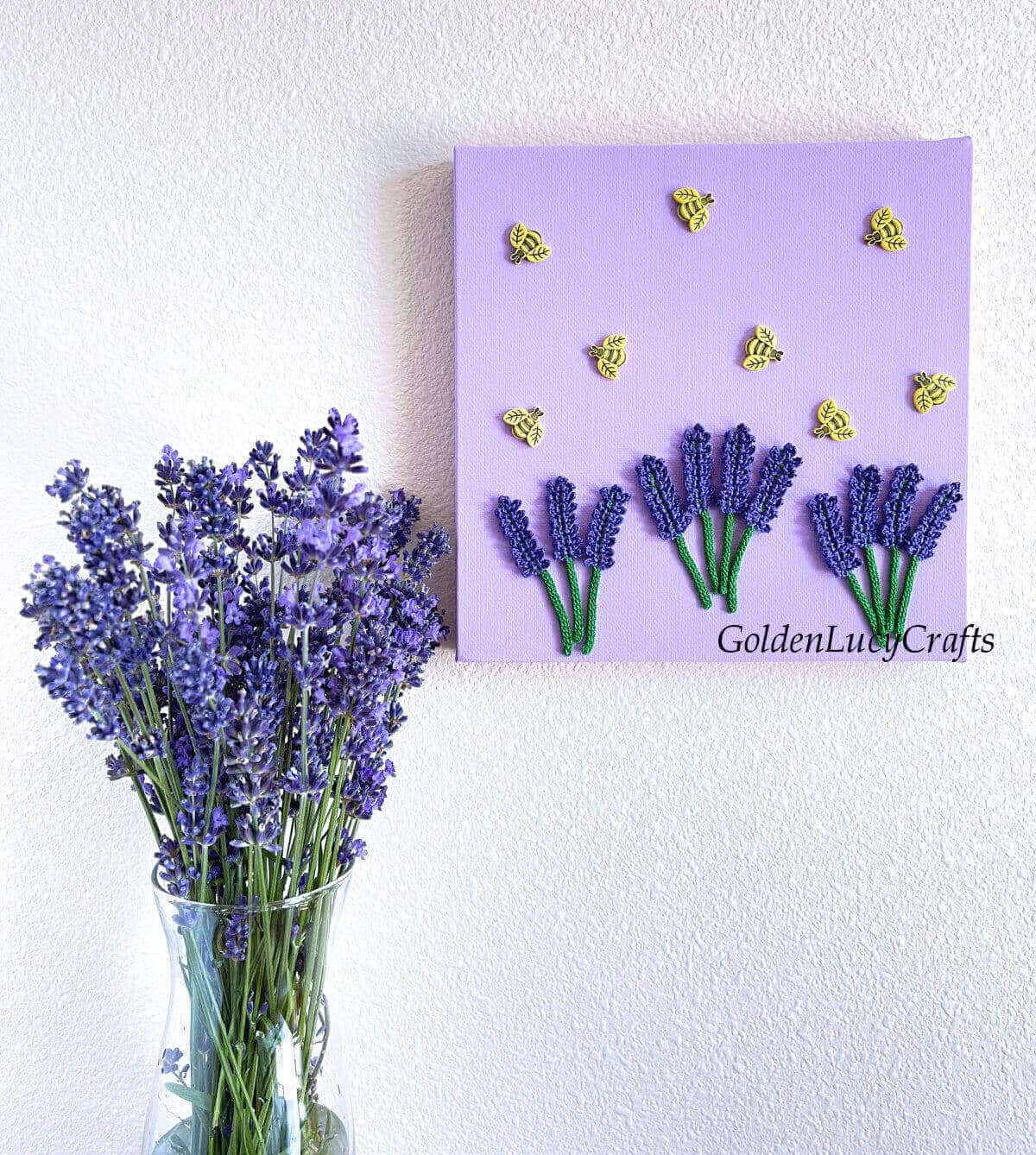 Wall art lavender and bees on the wall, lavender in the vase next to it.
