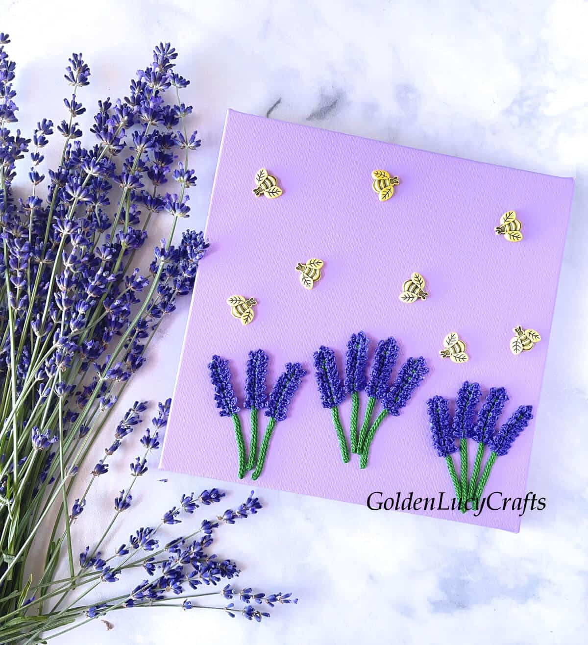 Crocheted lavender and bee buttons on the canvas.
