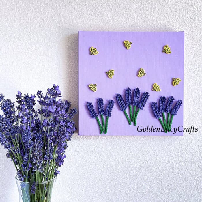 Wall art lavender and bees hangning on the wall, lavender in the vase next to it.