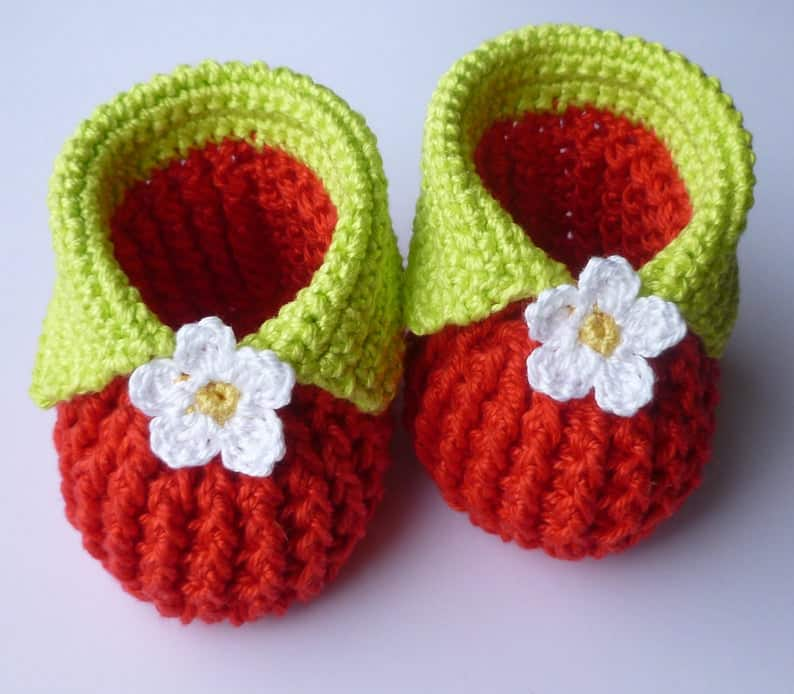 Red baby booties with green cuffs embellished with white flowers.