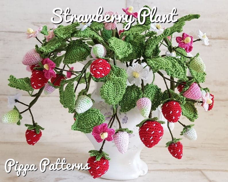Crocheted strawberry plant in a white vase.