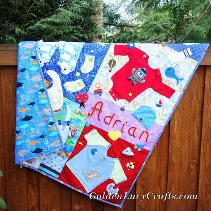 Baby clothes memory quilt hanging on the fence.