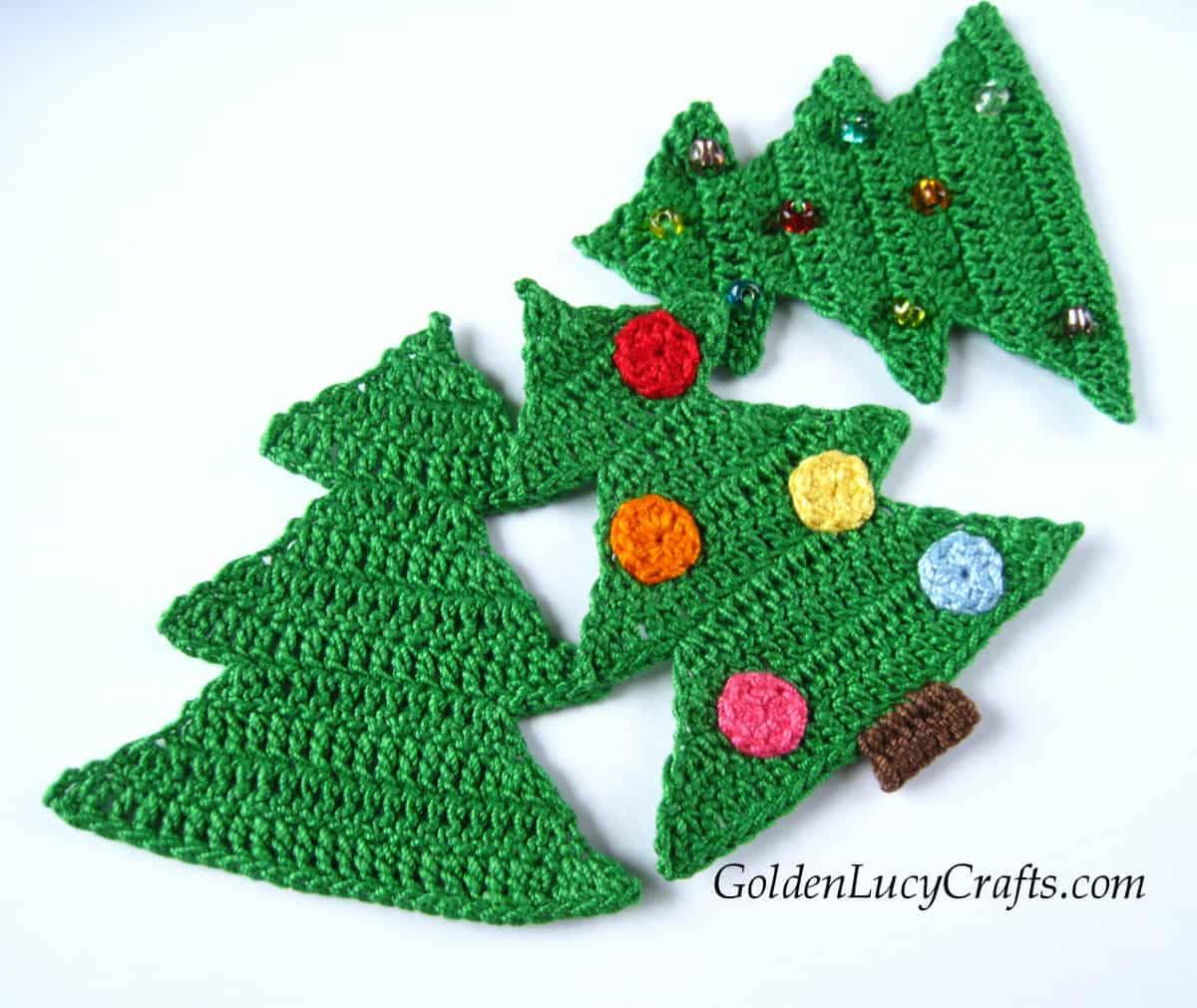 Three green crocheted Christmas tree appliques.