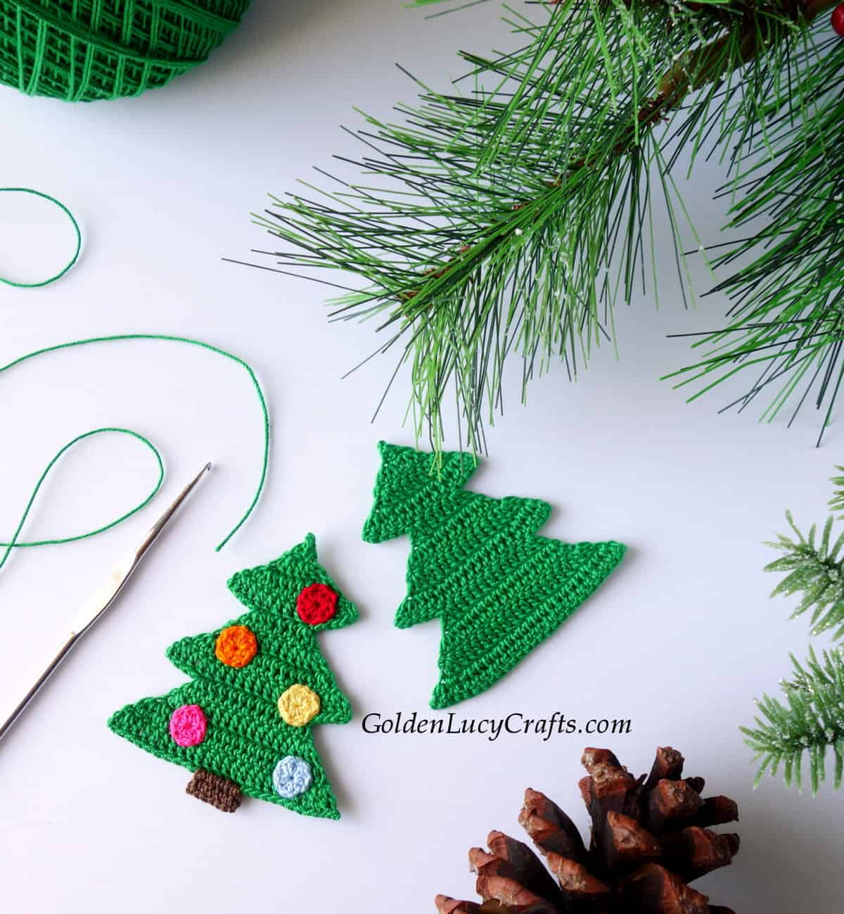 Two green crocheted Christmas tree appliques, crochet hook, green thread, fir tree branch and pine cone.