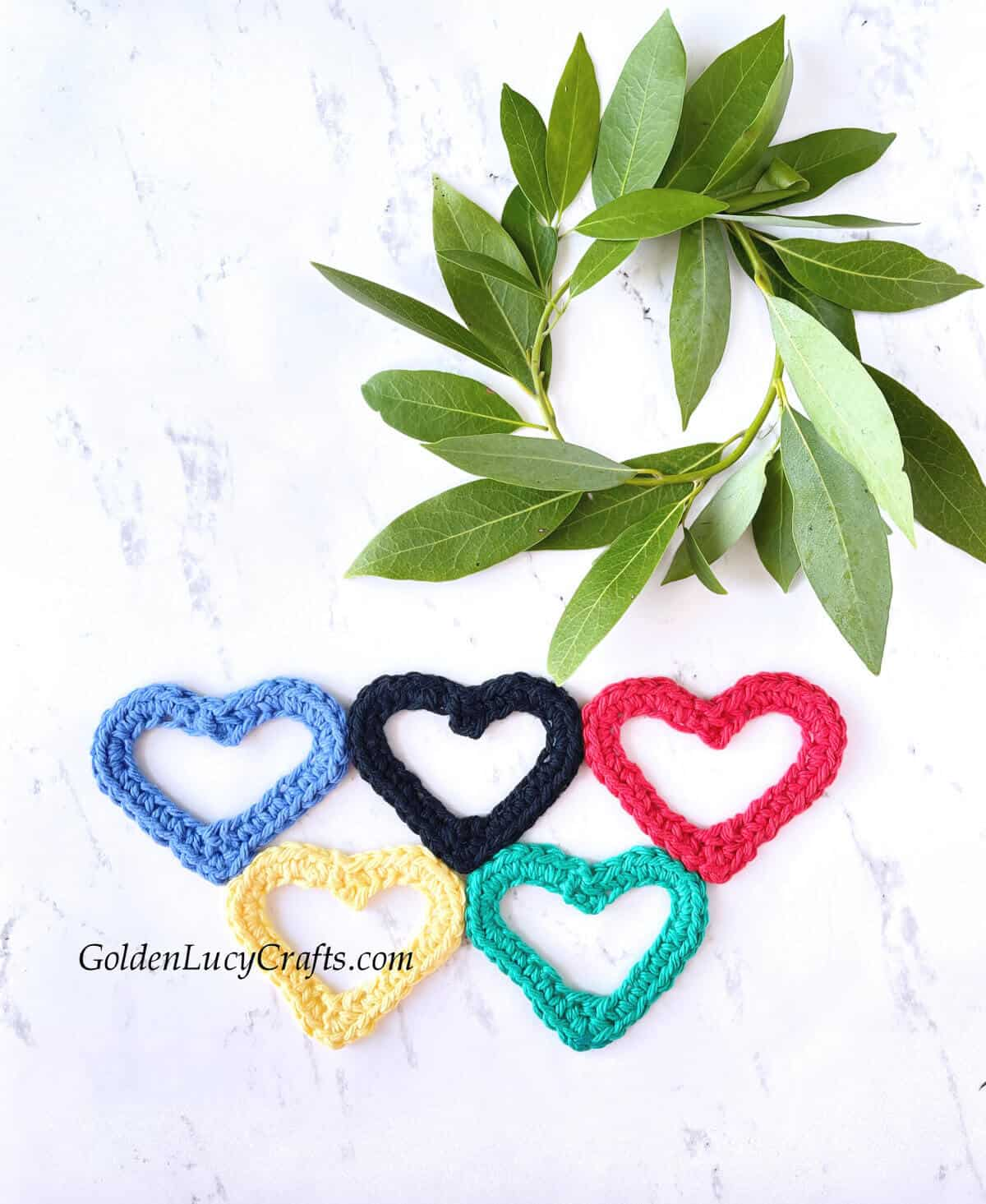 Crochet heart-shaped Olympic rings, round wreath made of green bay tree branch.