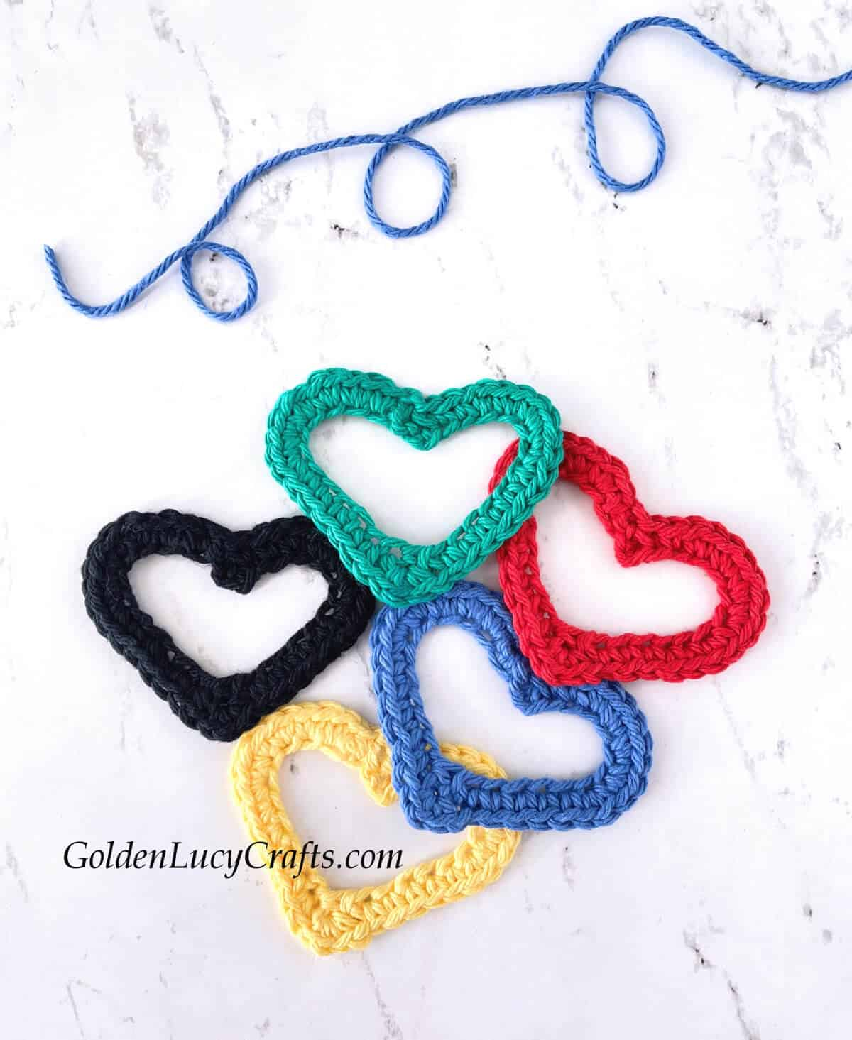 Crocheted hearts in red, blue, yellow, black and green colors.