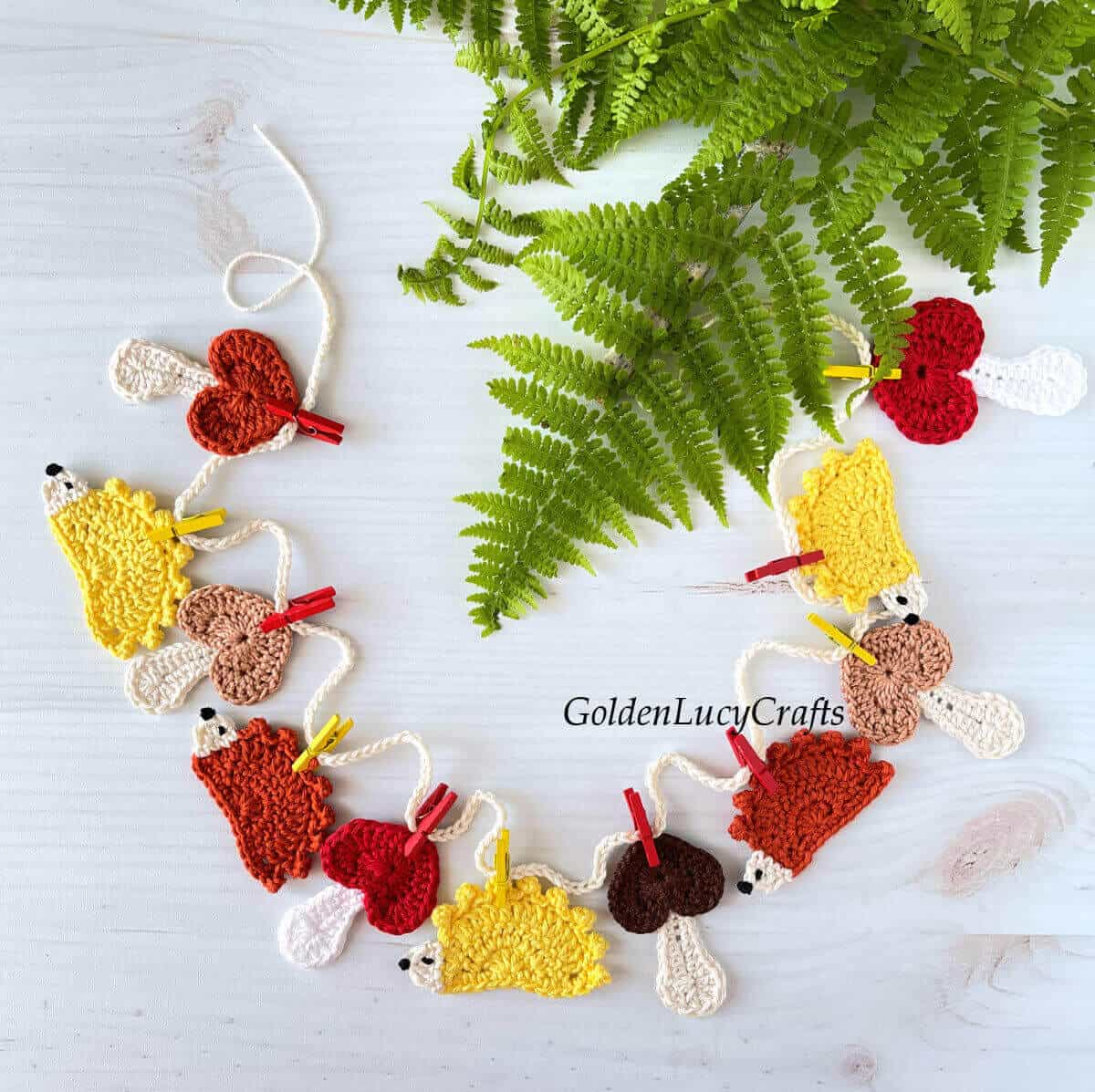 Crocheted mushrooms and hedgehogs garland, fern leaves in the background.