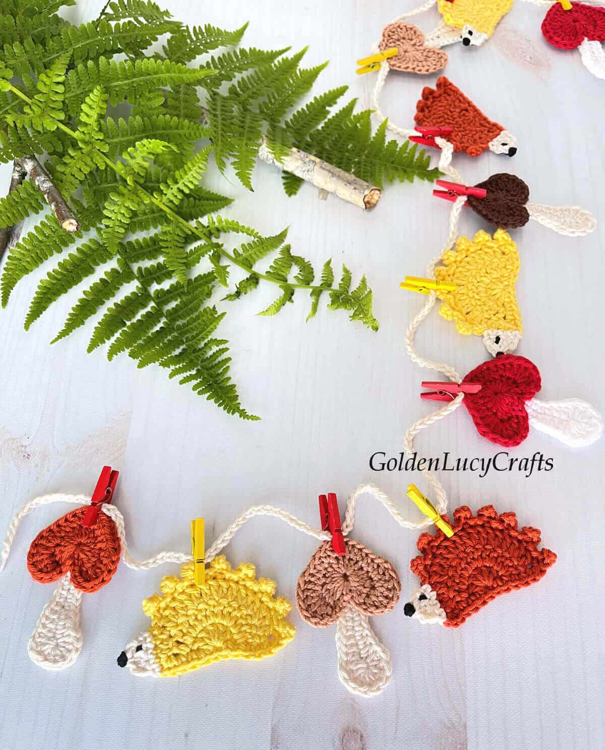 Crocheted mushrooms and hedgehogs attached with clothespins to the string.