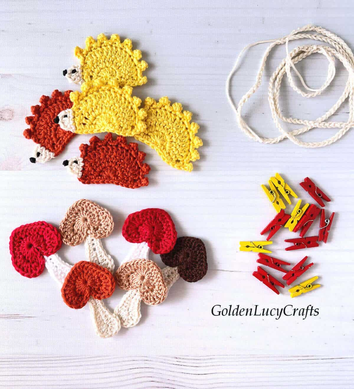 Crocheted hedgehog and mushroom appliques, red and yellow clothespins, crocheted string.