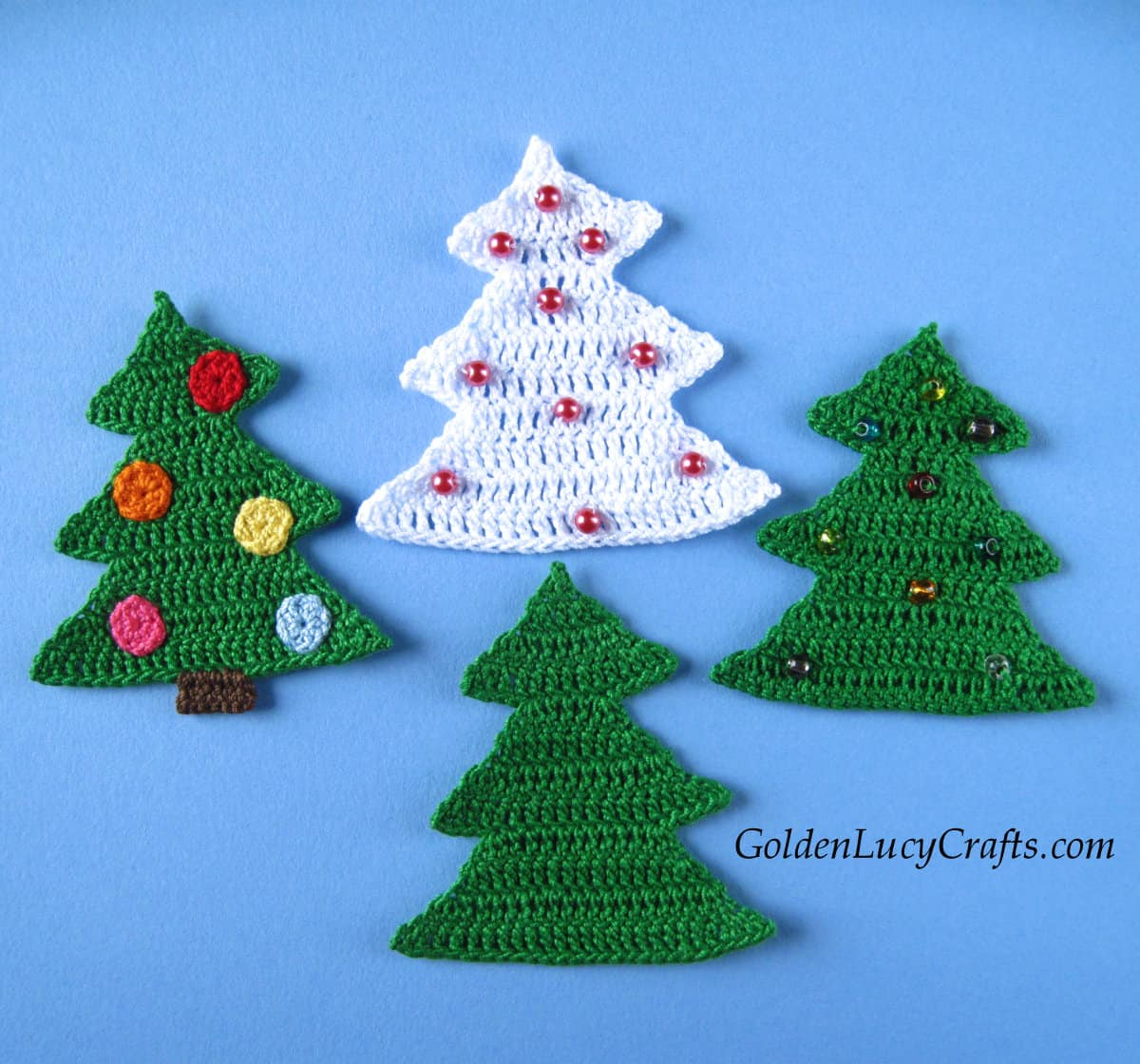 Three green and one white crocheted Christmas tree appliques.