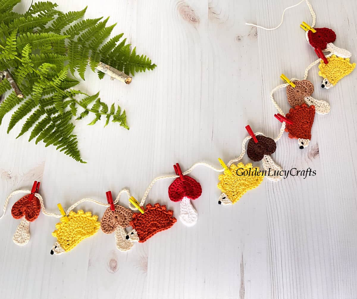 Crocheted garland forest themed hedgehogs mushrooms attached with small clothespins to the string.