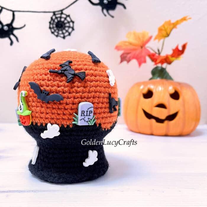 Crocheted Halloween snow globe, Jack-o'-lantern in the background.