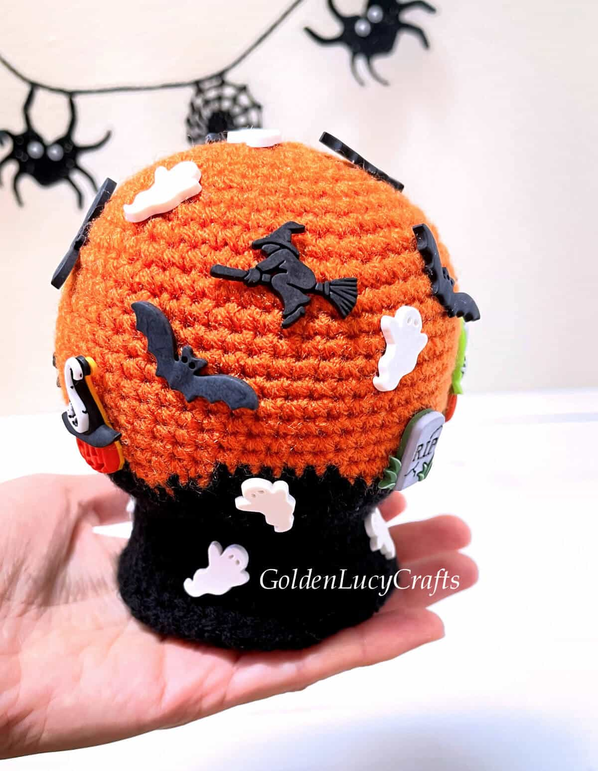 Crocheted Halloween snow globe in the palm of a hand.