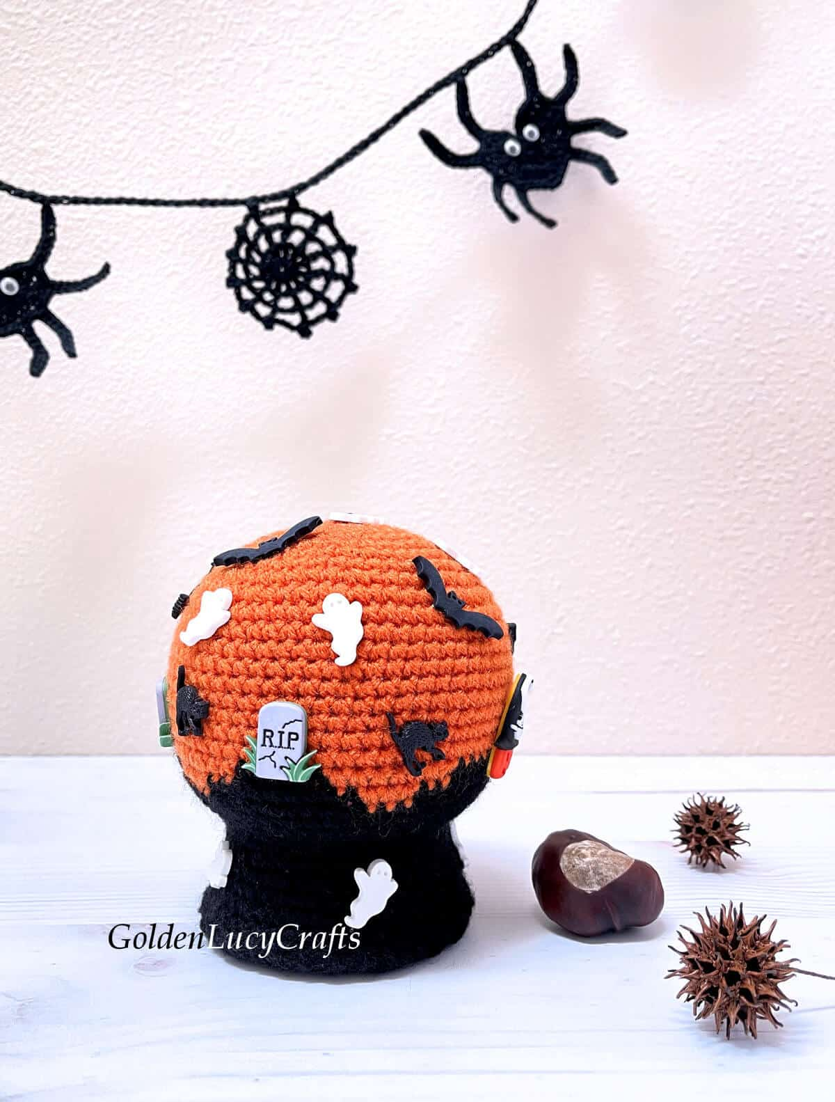 Crocheted Halloween snow globe embellished with craft buttons.