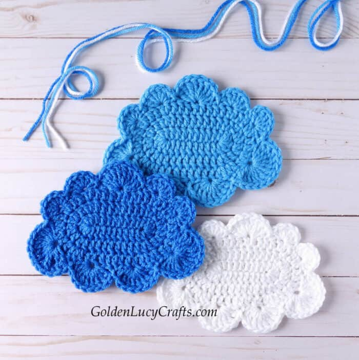 Three crocheted cloud appliques in white, blue and light blue colors.