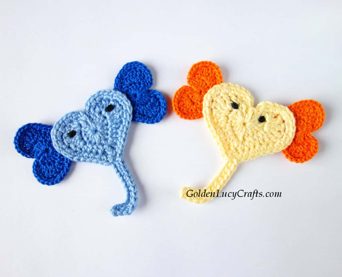 Two crocheted heart-shaped elephant appliques.