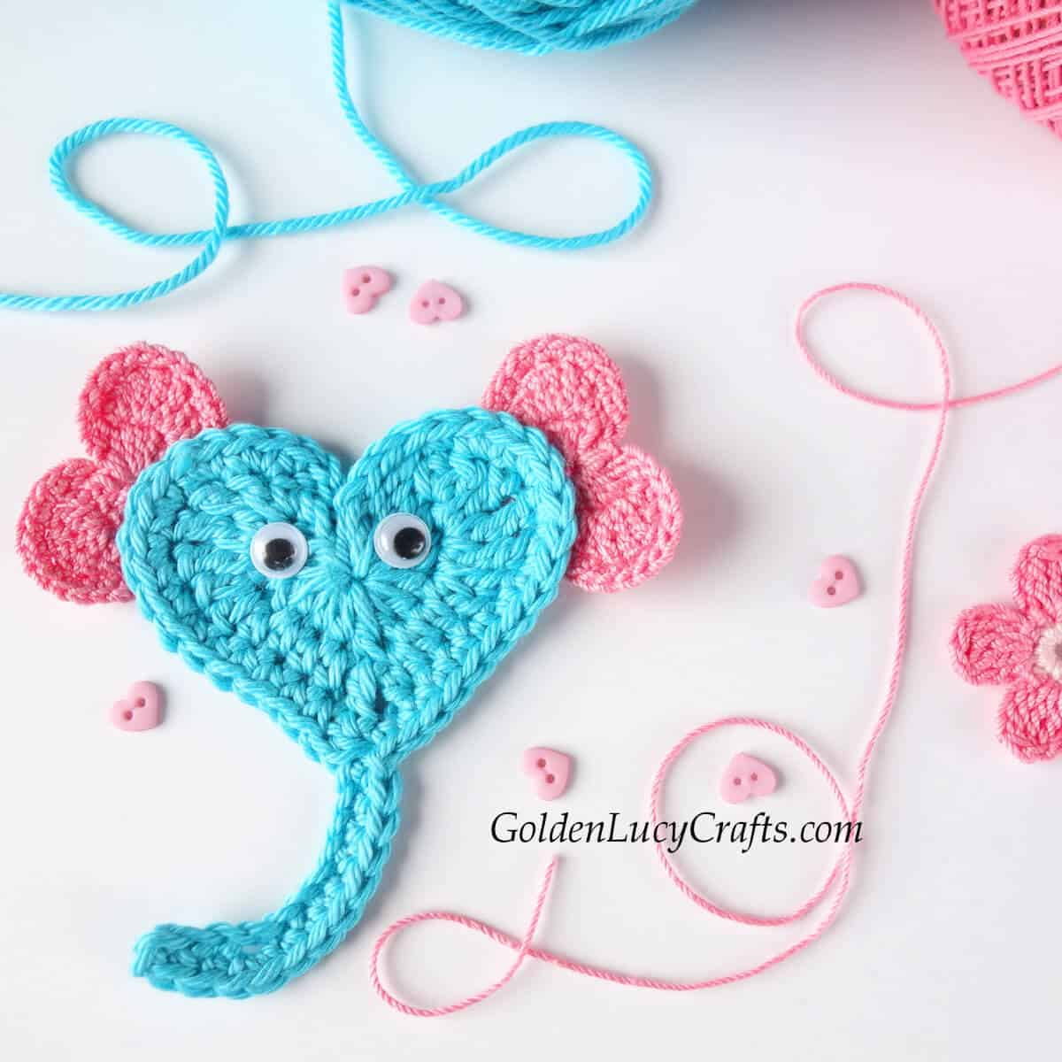 Crochet heart elephant applique in aqua with pink ears, close up picture.