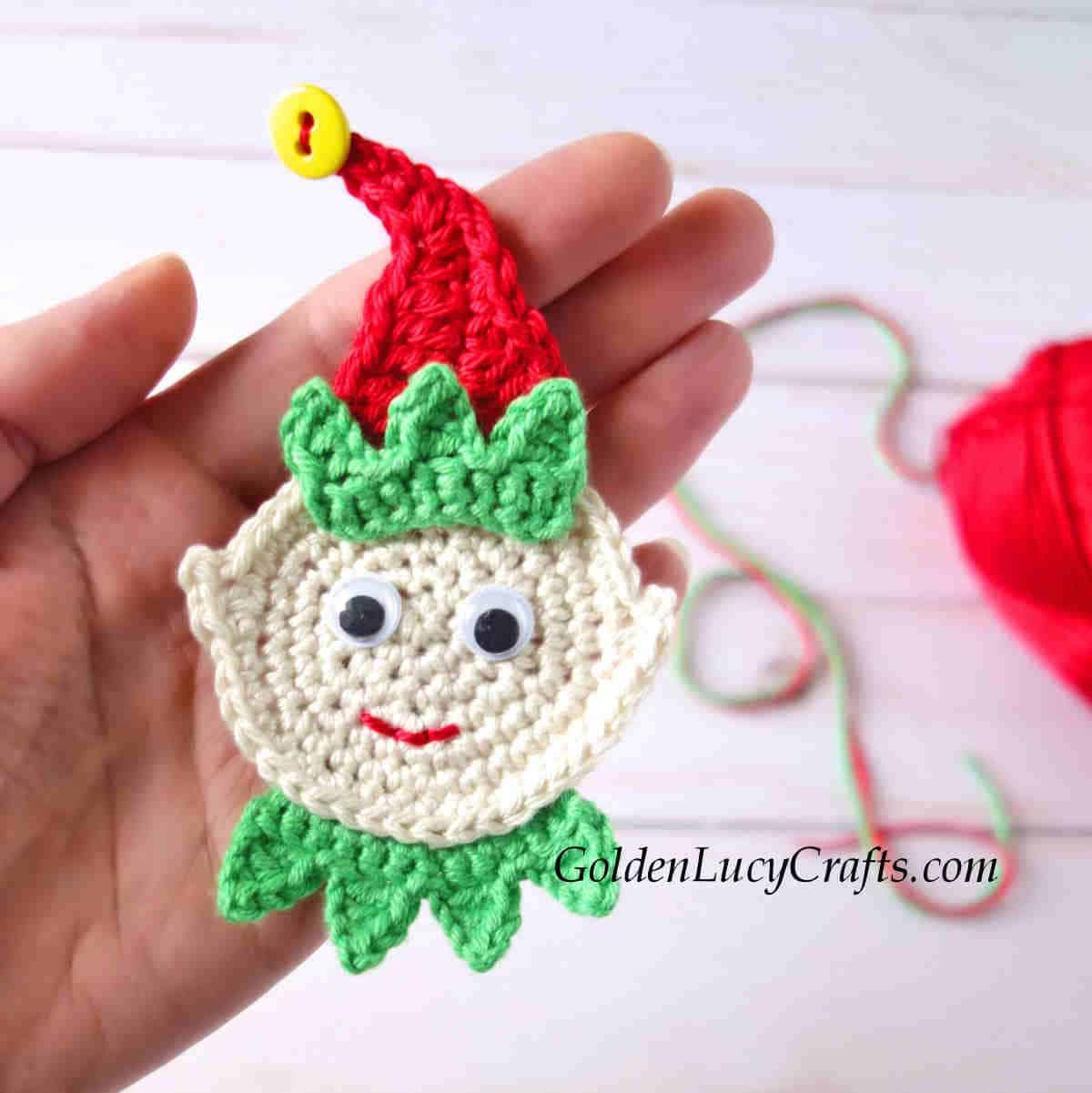 Crocheted elf applique in the palm of a hand.