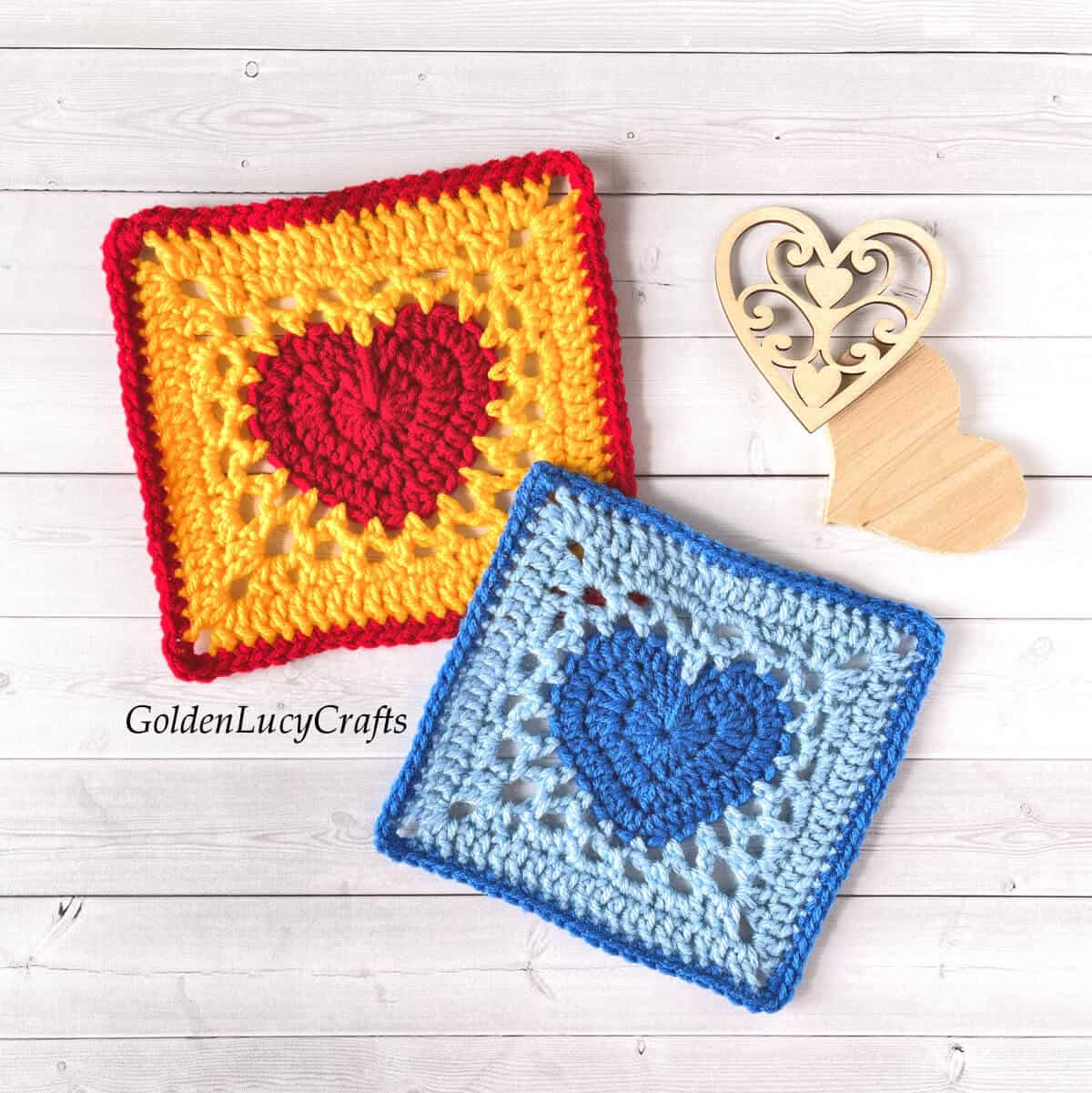 Two crocheted granny squares with heart in the middle of each.