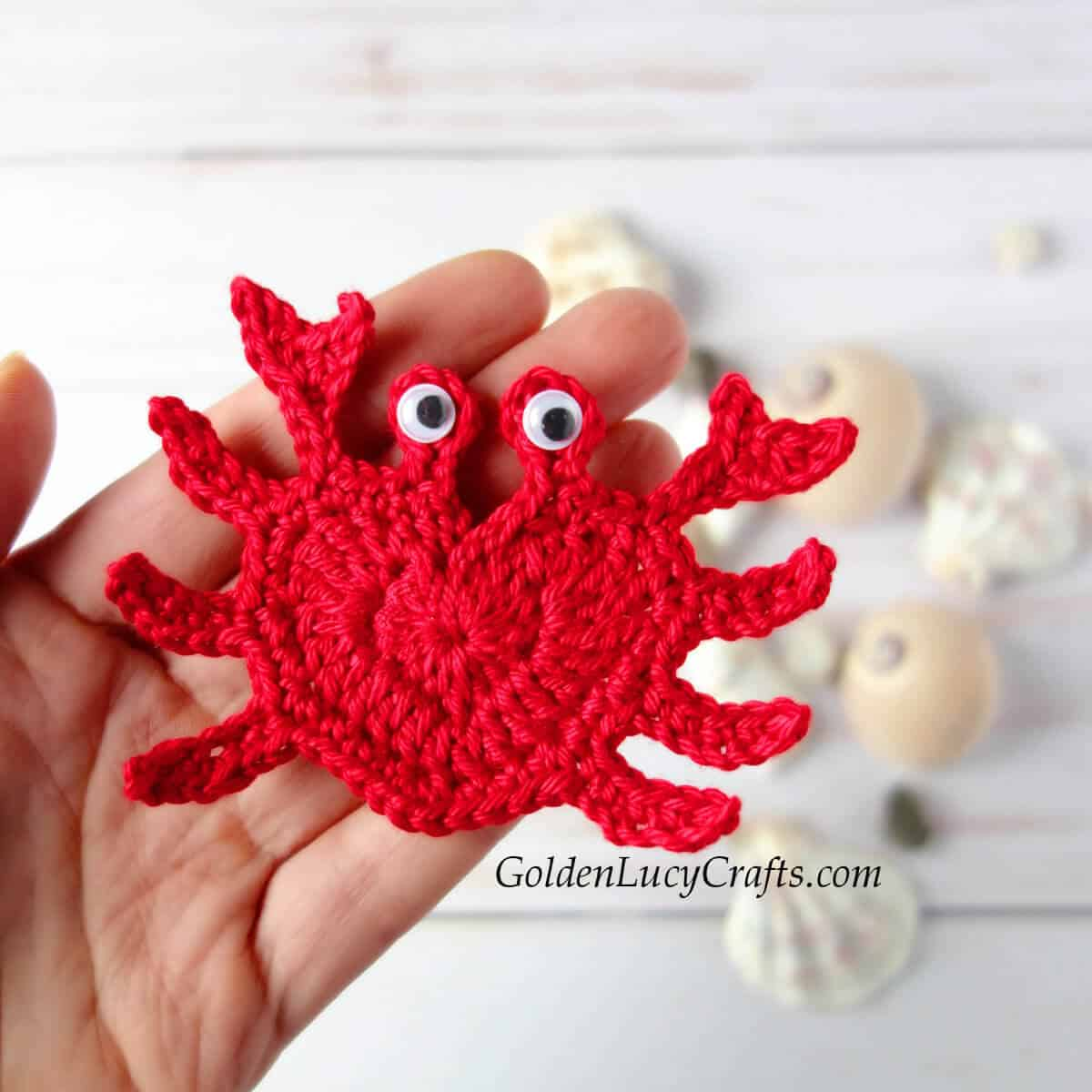 Crocheted red crab applique in the palm of a hand.