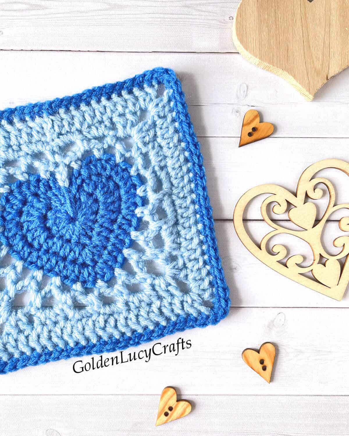 Blue crochet heart granny square close up picture, wooden hearts next to it.