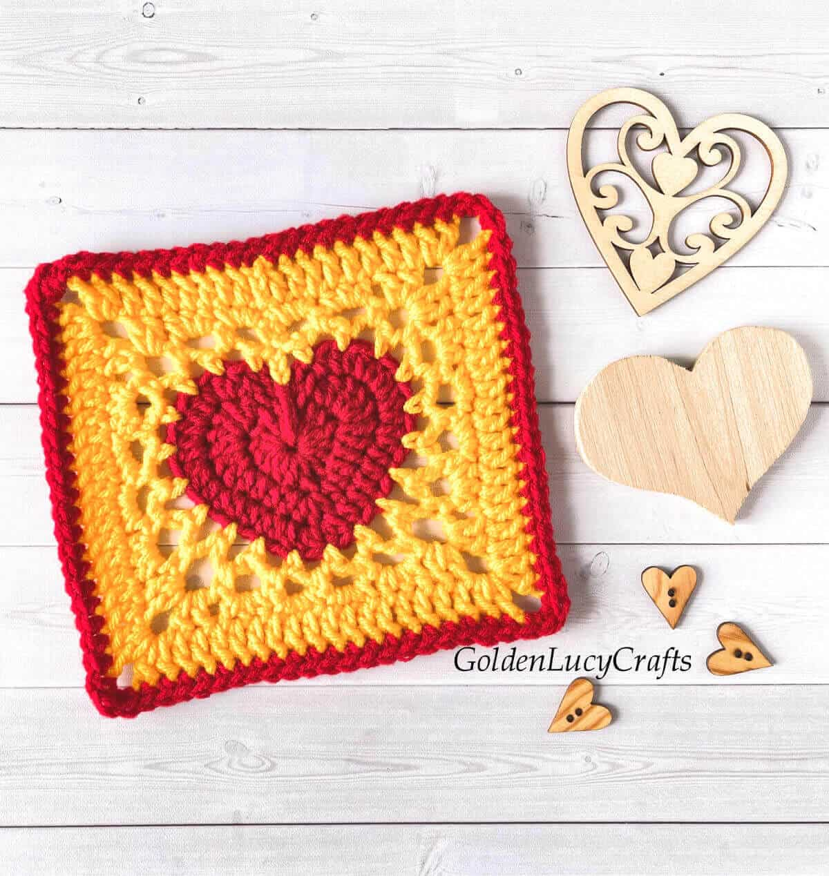 Red and yellow crocheted heart granny square, wooden hearts next to it.