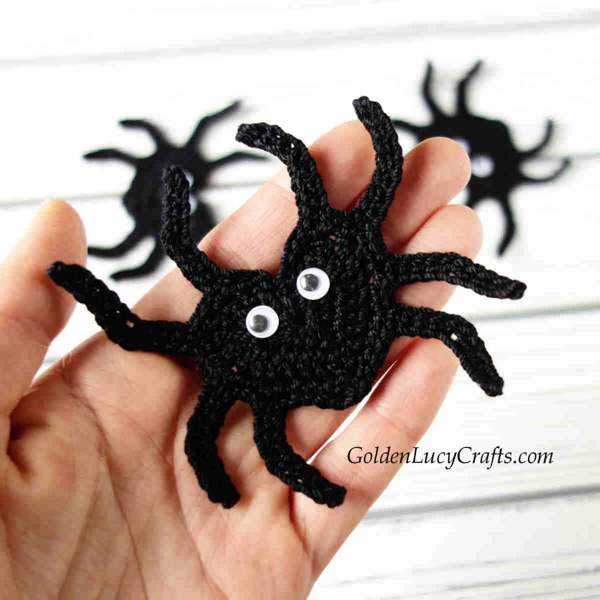 Crocheted black spider applique in the palm of a hand.