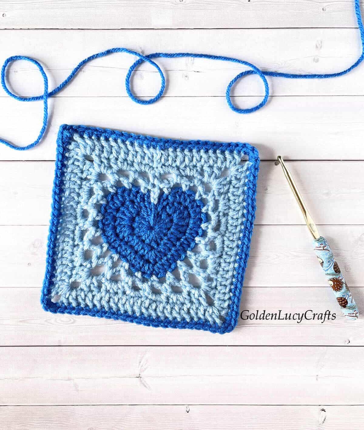 Blue crochet heart granny square, crochet hook and blue yarn.