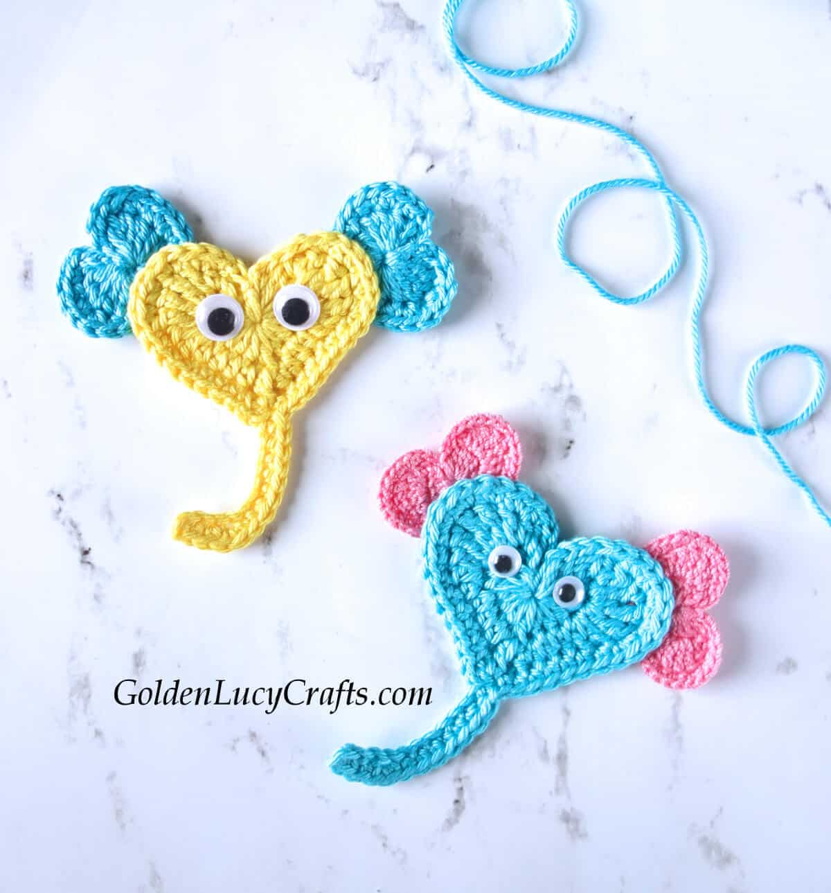 Two crocheted elephant appliques in yellow and blue colors.
