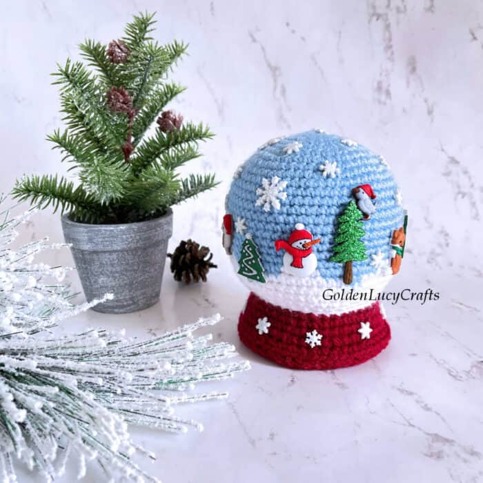 Crocheted snowglobe toy embellished with winter-themed buttons.