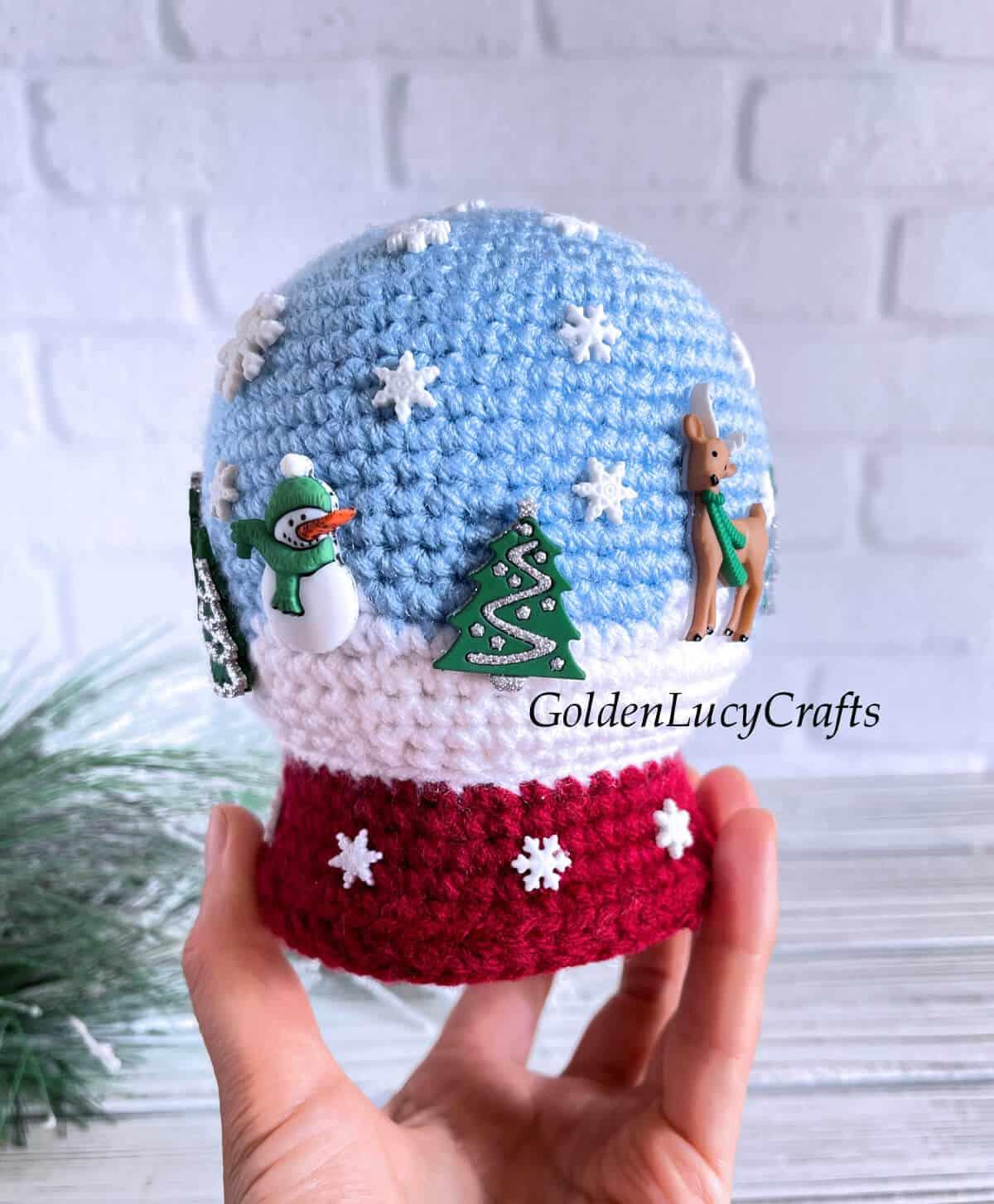 Crochet snowglobe amigurumi held by hand.