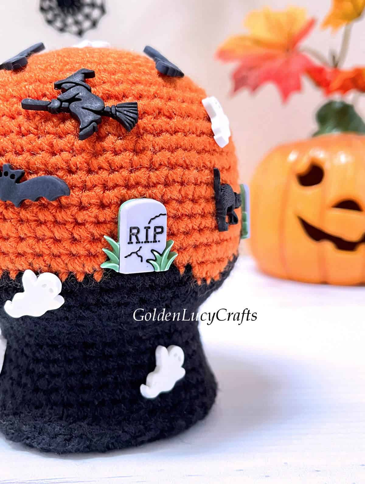 Crocheted Halloween snow globe close up picture, Jack-o'-lantern in the background.