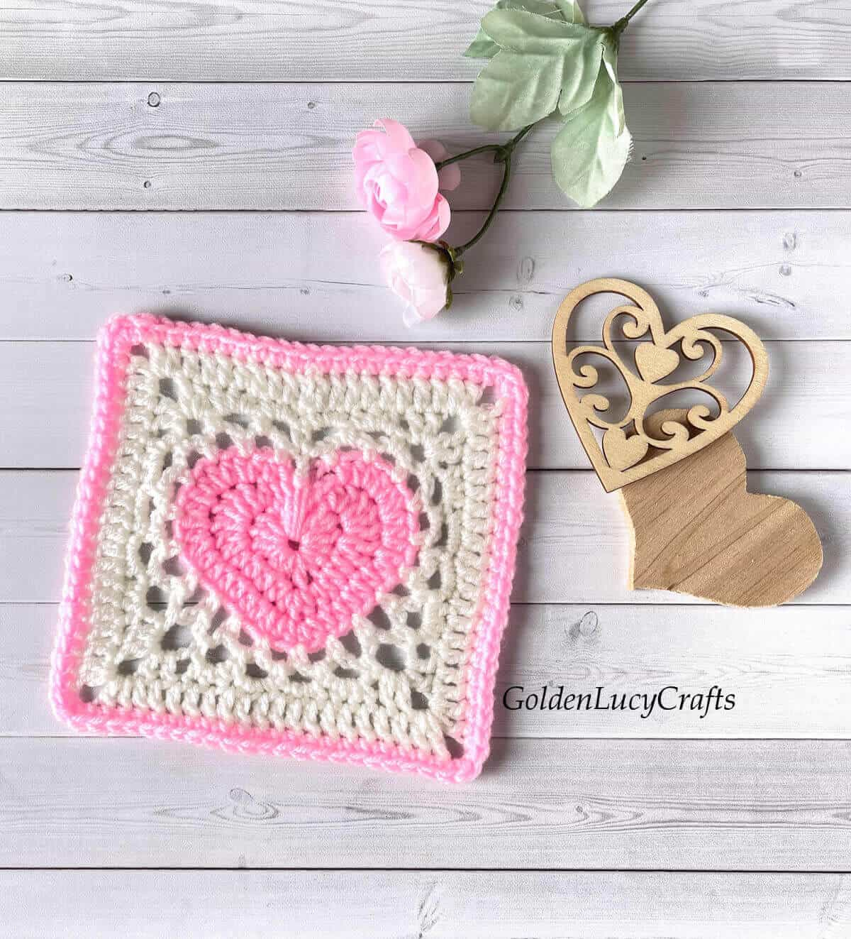 Pink and white crochet heart granny square, two wooden hearts and pink flower.