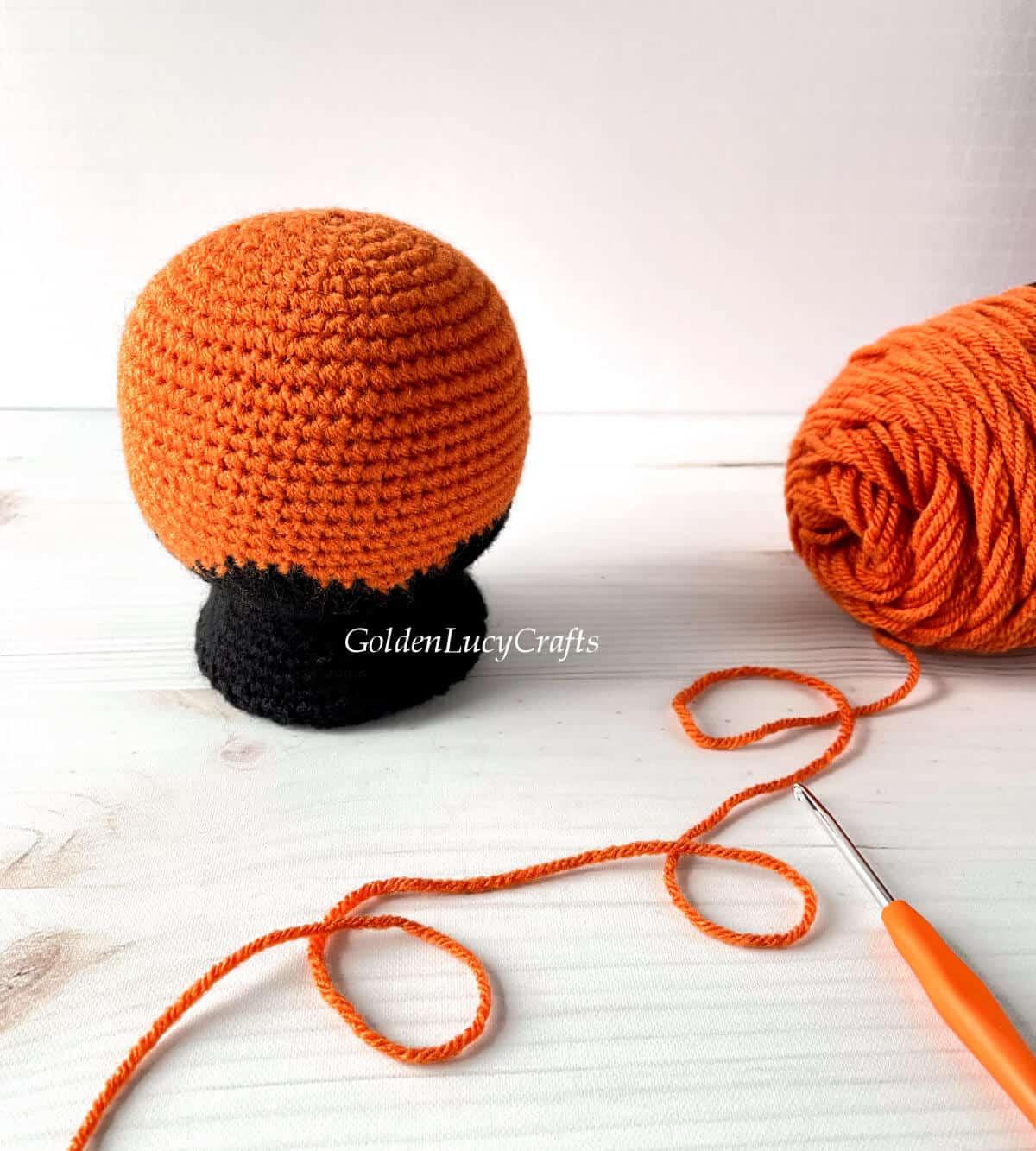Crocheted snow globe, orange yarn, crochet hook.