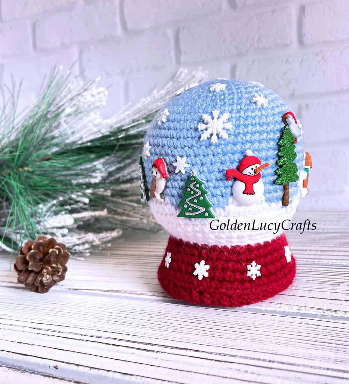 Crochet snow globe toy embellished with snowflakes, Christmas trees, snowmen and animals buttons.