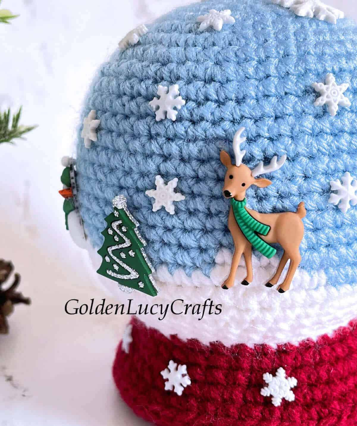 Crocheted snowglobe toy embellished with winter-themed buttons close up picture.