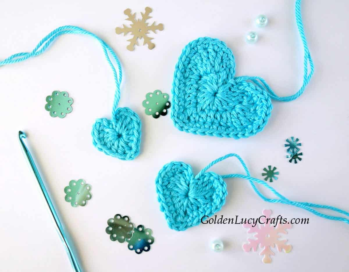 Three crocheted hearts in turquoise color.